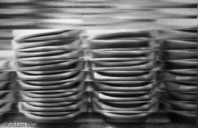 stacks of dishes behind frosted glass at Ollie's on Broadway & 67th Street. Handheld at 3200 ISO